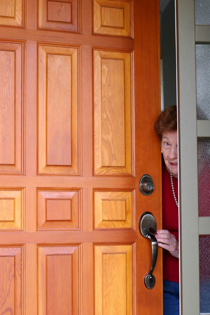 Seniorin schaut durch Tür